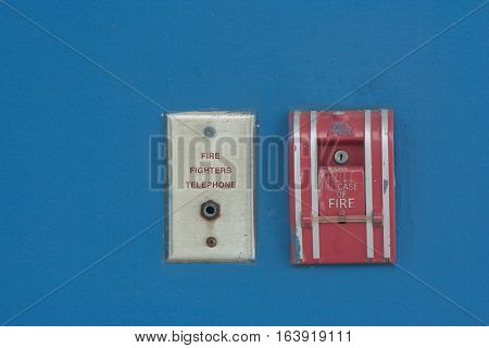 Fire Alarm and Fire Fighters Telephone on blue wall background.