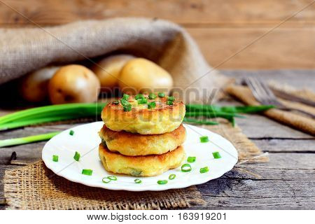 Fried vegetable cutlets. Potato cutlets with vegetables and spices on plate. Raw potatoes, fresh green onions, fork, knife on wooden table. Vintage style. Closeup. Tasty diet recipe