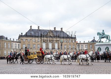 Copenhagen, Denmark - January 04, 2017: Queen Margrethe in her 24-carat golden coach escorted by the Guard Hussar Regiment is arriving at Amalienborg Palace