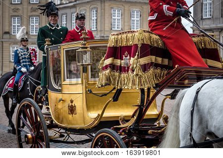 Copenhagen, Denmark - January 04, 2017: A smiling Queen Margrethe in her 24-carat golden coach escorted by the Guard Hussar Regiment is arriving at Amalienborg Palace