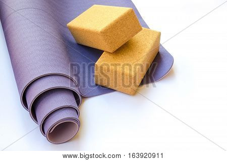 Yogi essentials. Lilac mat and two cork blocks on white background. Yoga practice concept. Copy space.