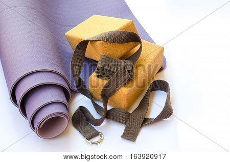 Yogi essentials. Lilac yoga mat two cork blocks and grey yoga strap on white background. Yoga practice concept.