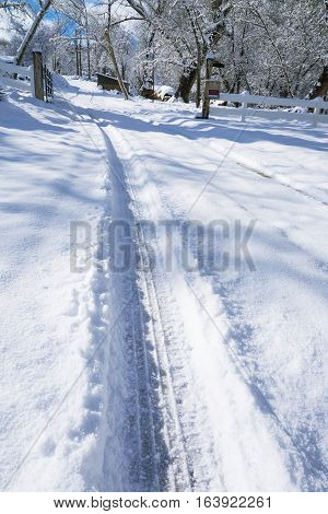 Tire Tracks in Snow 01 - A winter and snowy rural scene featuring tire tracks leading up through a residential property gate. The camera is primarily focused on the left hand track; adding to the perspective of the image. The background features a slight