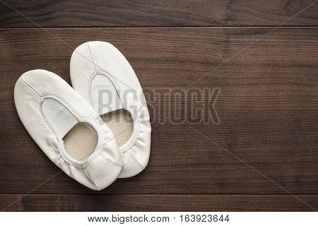 child's white dancing shoes on the wooden floor