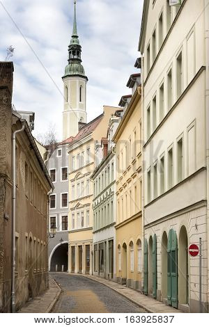 Picturesque alley in the town of Goerlitz, Germany, with the trinity church in the background