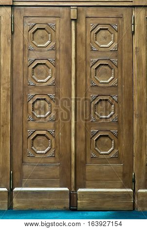 Close view of an elegantly carved light brown wooden door with octagonal pattern