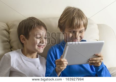 Children with tablet PC at home. Boys looking at screen smiling and playing games or watching video. People education learning technology leisure concept