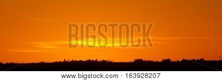 Nascer do sol (golden hour), com o céu em uma bela cor laranja.