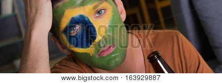 Closer shot of disappointed Brazil fan with a bottle of beer
