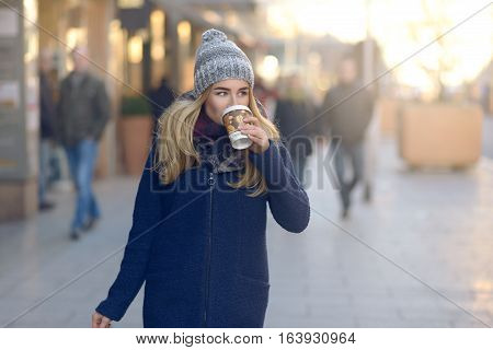 Woman Drinking Coffee And Walking In City