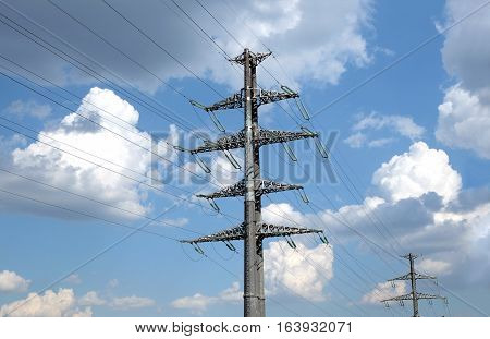 High-voltage power line gray metal props with many wires closeup view