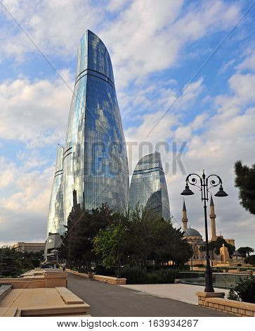 BAKU AZERBAIJAN - SEPTEMBER 25: Turkish mosque in front of Flame towers in Baku on September 25 2016. Baku is a capital and largest city of Azerbaijan.