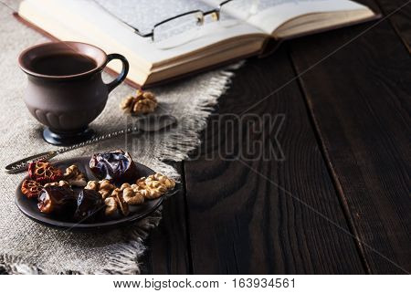 Cup of coffee and book on a wooden table
