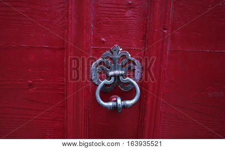 Background: fragment of a wooden door - boards painted in a dark blue red color and forged iron nails, door handle. Style Medieval Europe (France).