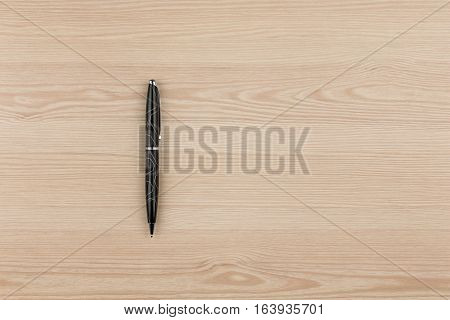 Black ballpoint pen lies on a wooden texture with place for your text