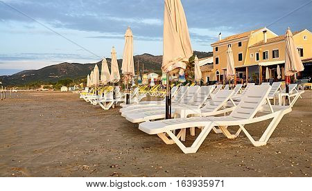 parasols and sun loungers on the beach near the sea