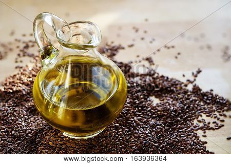 linseed oil in a glass jug and flax seeds on a wooden table healthy with omega 3 fatty acids selected focus narrow depth of field
