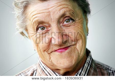 Granny face on a grey background. Grandmother