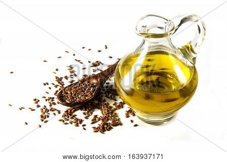 Brown flax seeds on a spoon and linseed oil in a glass jug isolated on a white background