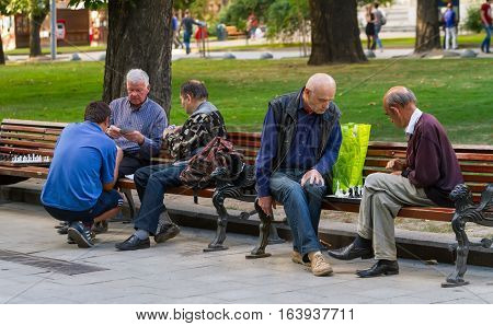Lviv Ukraine - July 15 2016. Two groups of men sitting on the benches in the park play chess and cards. Men play chess and cards.