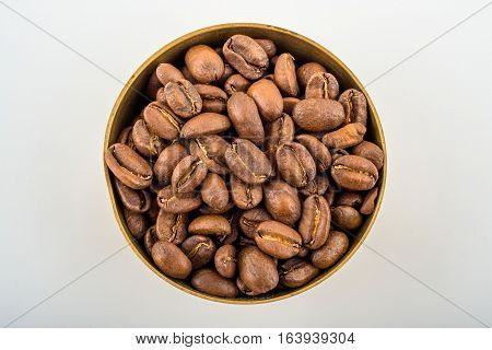 Roasted and fresh coffee beans in brass bowl