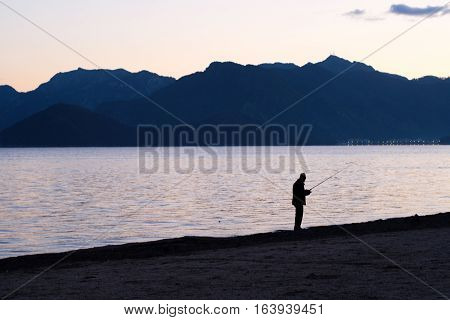 Silhouette Of Man Fishing On Beach