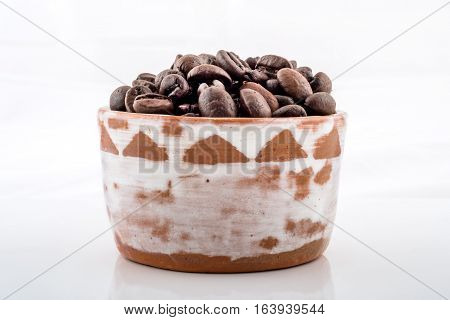 Roasted coffee beans in brown and white ceramic bowl