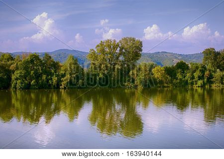 Surrealistic scenery, lake,trees and hills, purple and violet
