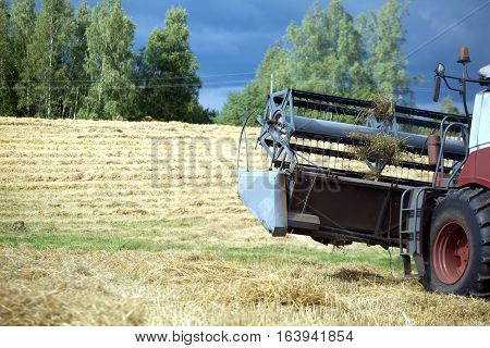Grain harvester rotary agricultural combine on field after harvest on background of a stormy sky on summer day. Photo closeup