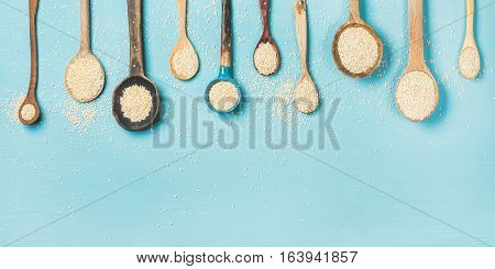 Quinoa seeds in different spoons over light blue background, top view, copy space, horizontal composition. Superfood, healthy eating, dieting, clean eating, detox or vegetarian food concept