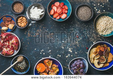 Ingredients for healthy breakfast over dark blue background, top view, copy space. Fresh and dried fruit, chia seeds, oatmeal, almonds, honey. Clean eating, vegan, healthy food, detox, dieting concept