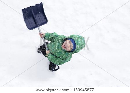 cheerful child removes snow shovel. happy boy laughs, enjoying the snow. view from above. empty space for your text