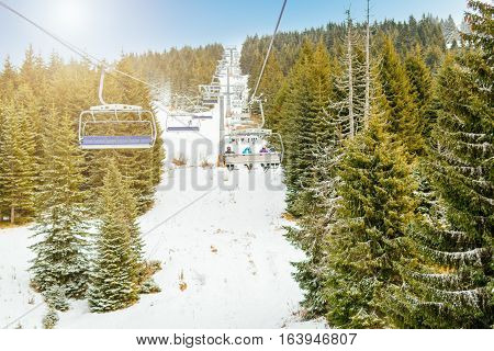 Ropeway and chair lifts in driving at ski resort in nice sunny day. Landscape.