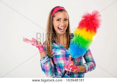 Portrait of a smiling young beautiful spring cleaning woman. She is holding a duster and looking at camera.