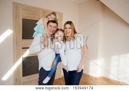 Cheerful family of four people. Young man holding in his arms his two daughters. Pregnant wife snuggles on husband. All great fun.