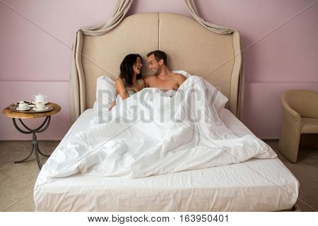 Couple in bed laughing. Cheerful man and woman. Romance and good mood.