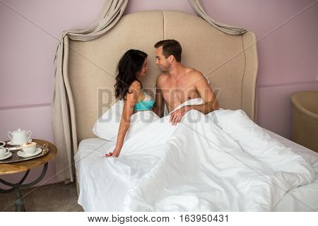 Caucasian couple in bed. Smiling man looks at woman. You belong with me.
