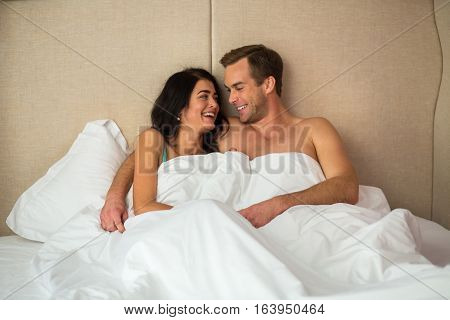Laughing couple in bed. Happy young woman and man. Are you joking.