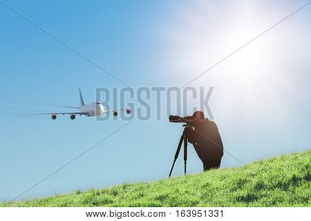 Silhouette of spotter photographer with camera and telephoto lens capturing photos of landing airliner. Aircraft or plane spotting is a hobby of tracking and monitoring the airplanes which is often accomplished by photography.