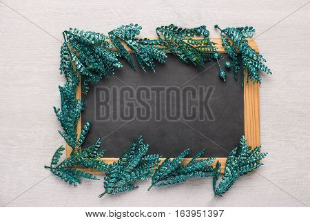 Nice frame of leaves of green glitter sparkles on slate background. Top view with copy space.
