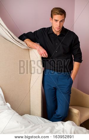 Young man standing in bedroom. Navy trousers and black shirt. Elegant clothes for men.