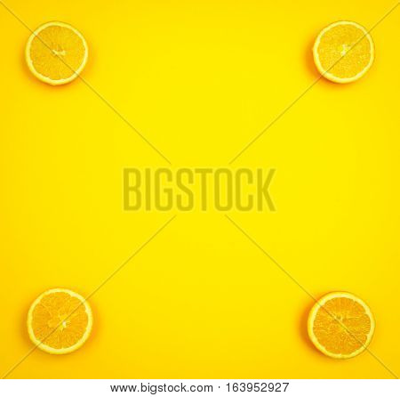 Orange slices in the corners of a yellowish background with copy space