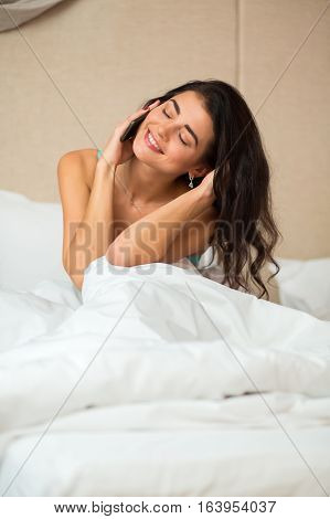 Female with phone in bed. Smiling girl holding smartphone. Hear the beloved voice.