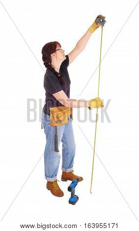 A tall middle age woman in jeans and a tool belt and drill measuring for her job standing isolate for white background.