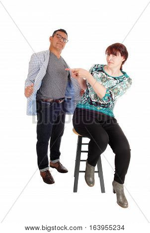 An wondering woman sitting on a chair pointing back at her standing husband looking pussled isolated for white background.
