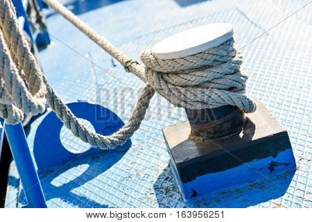 Rope tied to steel bollard on deck in natural light