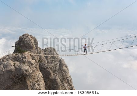 Man crossing the chasm on the hanging bridge (focus on the man)