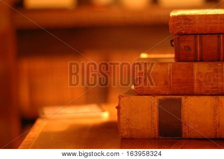 The edge of a pile of four old books on a warmly lit table.