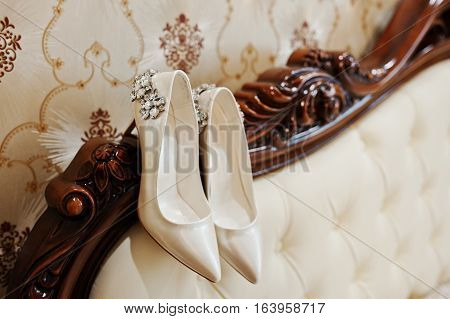 Elegancy Wedding Shoes Of Bride With Brilliant Brooch On The Bed