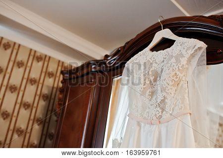 Amazing Wedding Dress On Hangers At Wooden Closet On Room Of Bride.